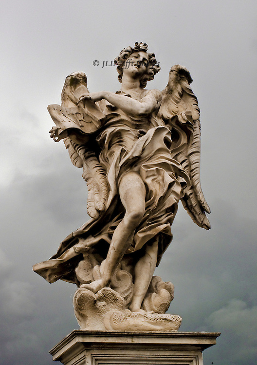 Statue of an angel on the Ponte Sant'Angelo, Rome.  The figures, carrying the instruments of Christ's passion, were executed by Bernini's pupils (Antonio Raggi, Antonio Giorgetti and Ercole Ferrata) between 1660 and 1668 to Bernini's design.  This one holds a scroll INRI, expressing symbolic pain under its flying robes and wings.  Cloudy, rain-filled sky above and behind the figure.