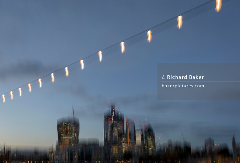 Blurred overhead lights on the Southbank and the skyline of the City of London - the capital's financial district (aka The Square Mile), on 29th October 2018, in London, England.