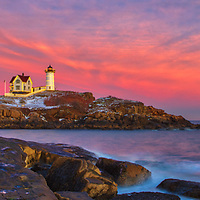 Nubble Lighthouse with Holiday Lighting Decoration taken at sunset in York, Maine. Loved watching this sunset burst into colors and capturing the Holiday Lights while the last light of the day created a beautiful sky across one of Maine's most iconic Christmas light scenes.<br />