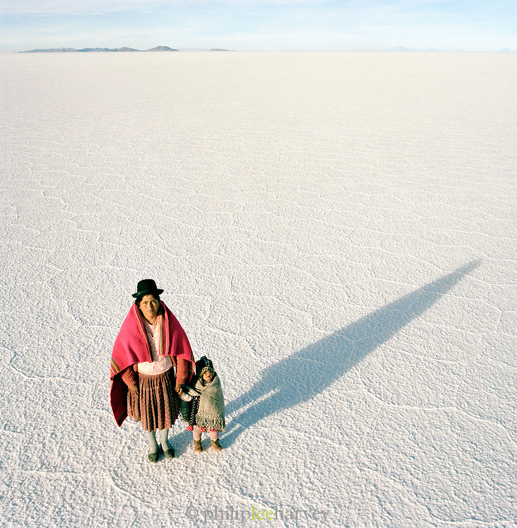 Portrait of woman with young boy in traditional dress on Salar de Uyuni salt flats, Bolivia. The Salar de Uyuni are the worlds largest salt flats.