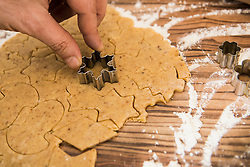 Close-up of a man cutting out snowflake shape cookies, Munich, Bavaria, Germany