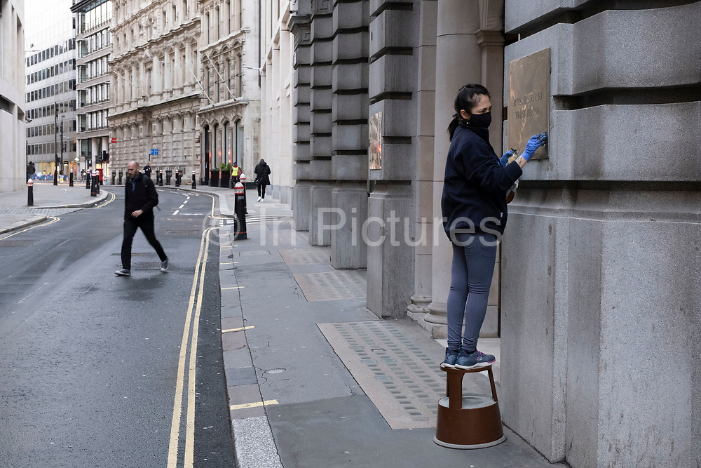 Cleaner polishing a brass plaque in the City of London on 29th January 2021 in London, United Kingdom. The financial district is home to many corporate headquarters, like here at Mitsubishi UFJ Financial Group, which is a leading global financial services group and one of the largest banking institutions in Japan.