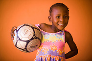 A young girl poses with her new soccer ball she received for her birthday in Gaborone, Botswana.