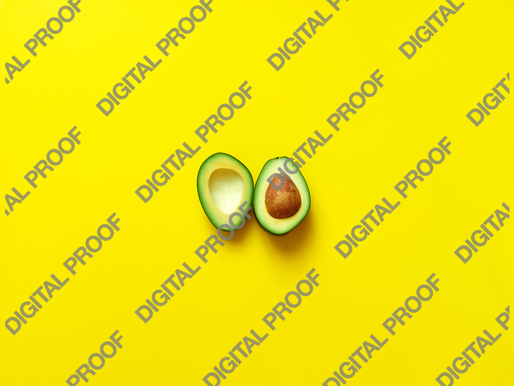 Avocado sliced with seed isolated in yellow background viewed from above - flatlay look