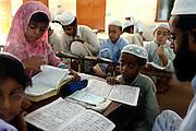 Muslim children are studying the Koran, Islam's holy book, at a large Madrassa (Islamic school) in North-West Karachi, Pakistan's main economic hub.