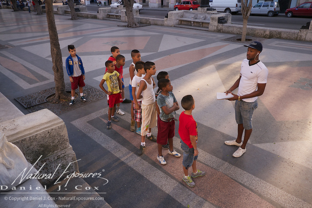 Children doing morning exercises on the Paseo del Prado, walkway that divides Centro Habana and Old Havana, Cuba.