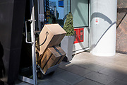 An Amazon Pantry delivery trolley is manoeuvred backwards through the door of offices in Aldwych in east London, on 1st April, 2019, in London England.
