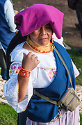 """A woman with purple head covering sells a cow at the bustling Saturday animal market in Otavalo, Ecuador, South America. The culturally vibrant town of Otavalo attracts many tourists to a valley of the Imbabura Province of Ecuador, surrounded by the peaks of Imbabura 4,610m, Cotacachi 4,995m, and Mojanda volcanoes. The indigenous Otavaleños are famous for weaving textiles, usually made of wool, which are sold at the famous Saturday market and smaller markets during the rest of the week. The Plaza del Ponchos and many shops tantalize buyers with a wide array of handicrafts. Nearby villages and towns are also famous for particular crafts: Cotacachi, the center of Ecuador's leather industry, is known for its polished calf skins; and San Antonio specializes in wood carving of statues, picture frames and furniture. Otavaliña women traditionally wear distinctive white embroidered blouses, with flared lace sleeves, and black or dark over skirts, with cream or white under skirts. Long hair is tied back with a 3cm band of woven multi colored material, often matching the band which is wound several times around their waists. They usually have many strings of gold beads around their necks, and matching tightly wound long strings of coral beads around each wrist. Men wear white trousers, and dark blue ponchos. Otavalo is also known for its Inca-influenced traditional music (sometimes known as Andean New Age) and musicians who travel around the world. Published in """"Light Travel: Photography on the Go"""" book by Tom Dempsey 2009, 2010."""