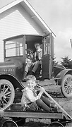 9133-01. Mr. Plank, of the Plank Jersey Dairy in Eugene, Oregon, with his son in their yard, with a new Sherwood Spring coaster wagon.