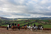 Members of a local hunt pause to admire the view from Hergest Ridge with their horses overlooking the Welsh/English border between Gladestry and Kington. Stopping on one the points with a fine panorama of Welsh valley below, the riders have descended the 426 metres high ridge which inspired an album by English multi-instrumentalist Mike Oldfield, Hergest Ridge: So if you feel a little glum, to Hergest Ridge you should come. In summer, winter, rain or sun, its good to be on horseback.