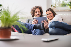 Couple using digital tablet at home, Munich, Bavaria, Germany