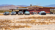 Abandoned Desert Home with Old Cars Parked in Front