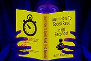 """Man crosses his eyes while reading a glowing booked titled """"Learn How To Speed Read In 60 Seconds"""".Black light"""