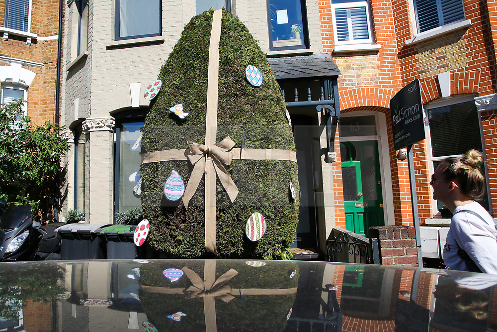 © Licensed to London News Pictures. 05/04/2020. London, UK. A woman looks at a hedge in the front garden of a house in Haringey, north London which is decorated as an Easter Egg. Photo credit: Dinendra Haria/LNP