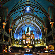 Interior and main altar of the Notre-Dame Basilica in the heart of Old Montreal. With the exterior modeled loosely on the famous Notre Dame de Paris, when the second tower was completed in the 1840s, the Basilica was the largest church in North America. It features dramatic interior lighting and exceptionally ornate decorating throughout along with a pipe organ consisting of 9000 pipes.