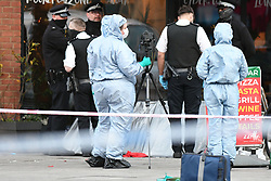 ©Licensed to London News Pictures; 23/04/2021, London UK; Police and Forensic officers at the scene of a murder in Barking road, Canning Town in Newham, East London. Officers were called just before 4.00 pm this afternoon after a 14 year old male was found with fatal stab wounds : Photo credit, Steve Poston/LNP