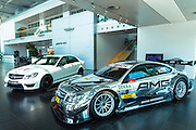 DTM Mercedes-AMG C-Coupe 2013 race car and white CLA 45 AMG with latest 4 cylinder engine on display in showroom at engine factory in Affalterbach, Germany