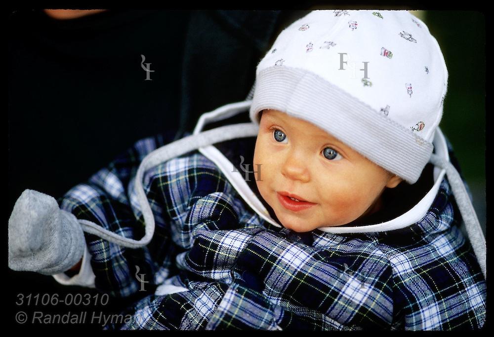Portrait of blue-eyed baby in cap and jacket; Clifden, Connemara, Ireland.