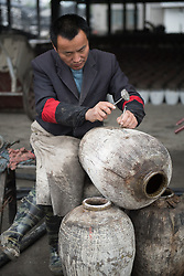 November 21, 2018 - Shaoxing, China - A worker repairs a rice wine jar at Shaoxing Nuerhong Winery Company in Shaoxing, east China's Zhejiang Province. The company maintains its traditional rice wine brewing method, which is composed of nearly 20 processing steps. (Credit Image: © Weng Xinyang/Xinhua via ZUMA Wire)