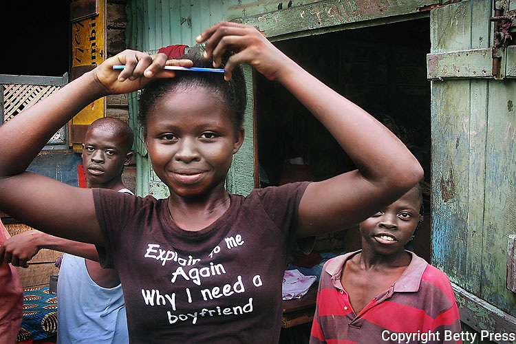 Young woman combing her hair.  She sports a TShirt that she bought in the used clothes market.