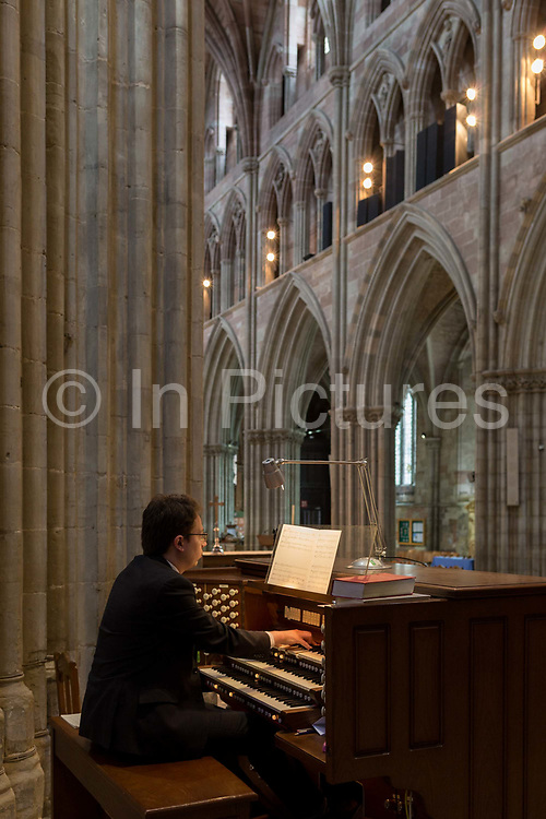 An organist plays his organ in the nave of Worcester Cathedral, on 23rd June 2019, in Worcester, England.