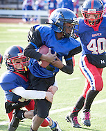 Newburgh, New York - A Middletown player tries to break away from a Goshen defender in the Orange County Youth Football League Division II Super Bowl at Newburgh Free Academy on Nov. 22, 2014.