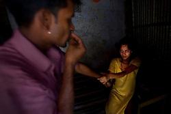 Sex worker Shetu, 17, asks a customer not to leave at brothel in Tangail, Bangladesh.