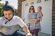 """GUNTERSVILLE, AL – SEPTEMBER 3, 2019: Brianna Barker, 34, watches her children as they play in the driveway. As the founder of Huntsville's chapter of the International Cesarean Awareness Network (ICAN), Barker facilitates support meetings and moderates online forums on topics surrounding cesarean birth in an effort to support mothers seeking a vaginal birth after cesarean (VBAC). <br /> <br /> Barker's first child was born prematurely by cesarean. Reflecting on the birth of Callen, her second child, Barker recalls feeling alone in her effort to have a normal vaginal birth. """"It was really hard. I didn't have a doula or any support network. Even today I have recurring nightmares where I'm alone in a dark hospital in labor. In my subconscious, I was just so alone."""" With their third and fourth children the Barkers chose an out of hospital birth experience – driving 2 ½ hours to Tennessee for every prenatal appointment. During this time, Barker was involved in the fight to legalize midwifery in Alabama. """"I knew I had many privileges that many others didn't have. So I went to Montgomery. And the other mom's and I – we all have this collective PTSD from dragging our screaming babies around Montgomery, marching to hearings and all that, just so there would be accountability. It's incredible the amount of barriers to access for v-backs, but I was able to have a vaginal birth with Callen, and for that I'm so grateful."""" <br /> <br /> Although midwifery has been legalized in Alabama, from Barker's perspective """"the fight is not really over."""" Today, many hospitals still ban vaginal births after cesarean. """"There's just so much misinformation, even about what the guidelines are,"""" Barker says. """"They're essentially mandating surgery for a large percentage of their patients, and I don't want that for other people. I want to make a difference, so other mom's can have the same experience I had. And if enough moms and families come together with more informati"""