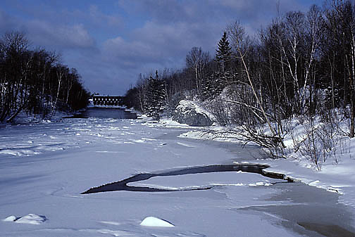 Jay Cooke State Park, snow covers semi-frozen St. Louis River new hydro dam. Winter.