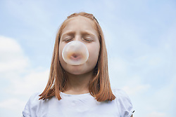 Girl blowing chewing gum bubble, Bavaria, Germany