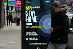 © Licensed to London News Pictures. 25/12/2020. London, UK. A man looks at the government's 'Stay Home- Tier 4' publicity campaign poster in north London amid fears of a third national lockdown after Christmas as COVID-19 infection rates rise. Many more areas of England will go into Tier 4 restrictions from Boxing Day as the mutated strains continue to spread throughout England. Photo credit: Dinendra Haria/LNP