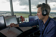 NATS Heathrow air traffic controller in control tower at Heathrow airport, London. Controlling aviation traffic on the ground and in the controlled airspace around London, the NATS controllers help safely guide up to 6,000 flights a day from the top of the 87 metre high tower, handling 1,350 aircraft movements a day into Heathrow. From the chapter entitled 'Up in the Air' and from the book 'Risk Wise: Nine Everyday Adventures' by Polly Morland (Allianz, The School of Life, Profile Books, 2015).
