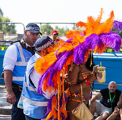 Police officers help a performer with her costume as day two of the Notting Hill Carnival in West London is in full swing, with performers floats forming the procession in what is known as Europe's Biggest Street Party. London, August 26 2019.