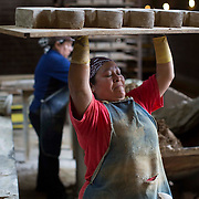 A employee at Carolina Brick lifts a tray of pavers over her head to take to the kiln.