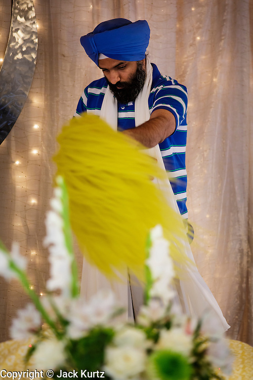 12 AUGUST 2012 - PHOENIX, AZ:   The Granthi waves a ceremonial fly whisk over the Guru during Sunday services at the Guru Nank Dwara Ashram Sikh temple in central Phoenix. Guru Nank Dwara Ashram is the oldest of three Sikh temples in the Phoenix area. There are about 1,500 Sikh families in the area. Memorials have been held throughout the week to honor the Sikhs killed in the mass shooting in Wisconsin last week. Sunday's service included several mentions of the massacre and was attended by a number of people active in the Phoenix interfaith community.   PHOTO BY JACK KURTZ