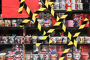 Cracked glass in the window of a tourist souvenir shop has been sealed over with striped diagonal tape. Taped haphazardly on the pane of glass, the yellow and black stripes give a hint of damage and danger should the glass break further and cut a passer-by. Inside the shop located near Leicester Square, we see mugs with various designs celebrating the Uk and British values including the Union jack and London cityscapes. The stripes make for abstract art.