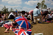 London, UK. Thursday 9th August 2012. London 2012 Olympic Games Park in Stratford. Fans with union jack flags rest in the sunshine.