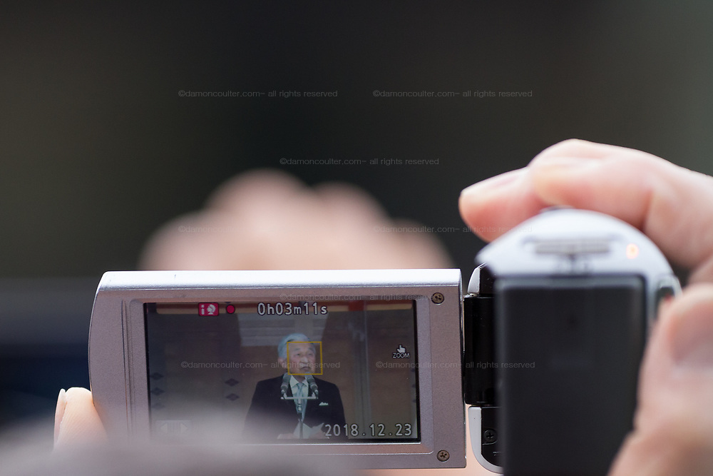 Emperor Akihito is recorded in a video camera of a well-wisher at the Imperial Palace to celebrate the 85th birthday of Emperor Akihito of Japan. The Emperor, who is the son of Japan's wartime leader, Emperor Hirohito, gave a speech to mark his last birthday before his upcoming abdication, saying he felt relief that his reign was coming to an end without having seen his country at war again and that it was important to continue to educate young people about japan's wartime past. Imperial Palace, Tokyo, Japan. Sunday December 23rd 2018