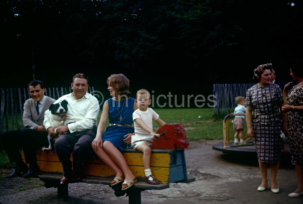 Family and friends sit on a rocking horse in a playground during summer time in the early 1960s. The portrait has been recorded on a film camera by the boy at the front's father, an amateur photographer in 1961. A man is holding on tight to a black and white pet sheepdog and two mothers chat on the right of the picture in this public park in Essex. The picture shows us a memory of nostalgia in an era from the last century.