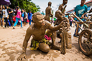28 JUNE 2014 - DAN SAI, LOEI, THAILAND: A man covered in mud from the Mun River sits in the street during the Ghost Festival parade in Dan Sai. Phi Ta Khon (also spelled Pee Ta Khon) is the Ghost Festival. Over three days, the town's residents invite protection from Phra U-pakut, the spirit that lives in the Mun River, which runs through Dan Sai. People in the town and surrounding villages wear costumes made of patchwork and ornate masks and are thought be ghosts who were awoken from the dead when Vessantra Jataka (one of the Buddhas) came out of the forest.    PHOTO BY JACK KURTZ