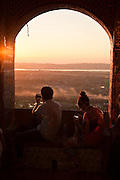 A couple takes mobiles pictures of the sunset from Mandalay Hill, Mandalay, Burma.<br />