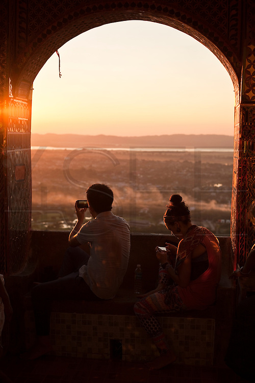 A couple takes mobiles pictures of the sunset from Mandalay Hill, Mandalay, Burma.<br /> Note: These images are not distributed or sold in Portugal