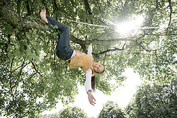 Girl hanging on tree and smiling, Munich, Bavaria, Germany