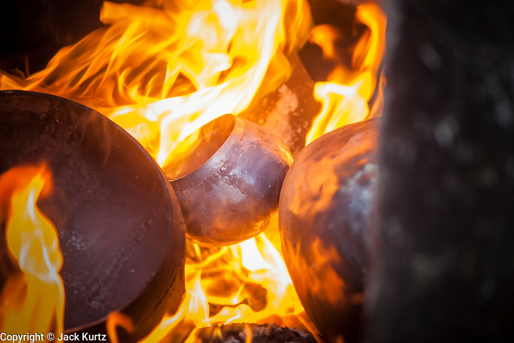 """03 DECEMBER 2012 - BANGKOK, THAILAND:  Monks alms bowls are fired on Soi Baan Bat in Bangkok. The bowls are made from eight separate pieces of metal said to represent the Buddha's Eightfold Path. The Monk's Bowl Village on Soi Ban Baat in Bangkok is the only surviving one of what were originally three artisan's communities established by Thai King Rama I for the purpose of handcrafting """"baat"""" the ceremonial bowls used by monks as they collect their morning alms. Most monks now use cheaper factory made bowls and the old tradition is dying out. Only six or seven families on Soi Ban Baat still make the bowls by hand. Most of the bowls are now sold to tourists who find their way to hidden alleys in old Bangkok. The small family workshops are only a part of the """"Monk's Bowl Village."""" It is also a thriving residential community of narrow alleyways and sidewalks.  PHOTO BY JACK KURTZ"""