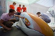 De VeloX3 wordt gecontroleerd na aankomst. Het Human Power Team Delft en Amsterdam is aangekomen in Battle Mountain en begint met de voorbereidingen. In Battle Mountain (Nevada) wordt ieder jaar de World Human Powered Speed Challenge gehouden. Tijdens deze wedstrijd wordt geprobeerd zo hard mogelijk te fietsen op pure menskracht. Ze halen snelheden tot 133 km/h. De deelnemers bestaan zowel uit teams van universiteiten als uit hobbyisten. Met de gestroomlijnde fietsen willen ze laten zien wat mogelijk is met menskracht. De speciale ligfietsen kunnen gezien worden als de Formule 1 van het fietsen. De kennis die wordt opgedaan wordt ook gebruikt om duurzaam vervoer verder te ontwikkelen.<br /> <br /> The Human Power Team Delft and Amsterdam has arrived in Battle Mountain and is preparing for the races. In Battle Mountain (Nevada) each year the World Human Powered Speed Challenge is held. During this race they try to ride on pure manpower as hard as possible. Speeds up to 133 km/h are reached. The participants consist of both teams from universities and from hobbyists. With the sleek bikes they want to show what is possible with human power. The special recumbent bicycles can be seen as the Formula 1 of the bicycle. The knowledge gained is also used to develop sustainable transport.