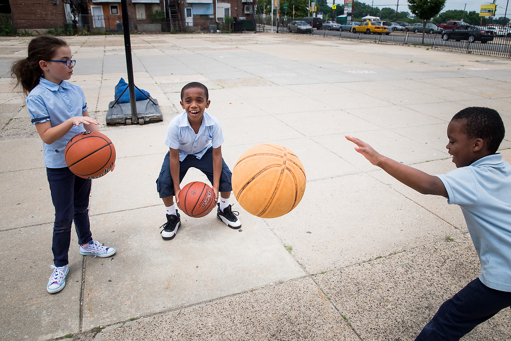 Amina Reeves, 8, Dominic James, 9, and Raymond Knighten, 8, play with basketballs at Patterson Elementary School in the Kingsessing neighborhood of Philadelphia, Pennsylvania on June 14 2017. Reeves' and James' basketballs were given to them by Mike Gibson, a process server in Philadelphia's Kingsessing neighborhood, who has become locally famous for giving out basketballs to children as he works.
