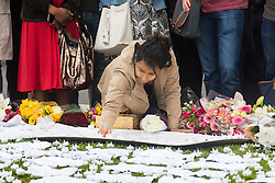 Parliament Square, Westminster, London, June 17th 2016. Following the murder of Jo Cox MP friends and members of the public lay flowers, light candles and leave notes of condolence and love in Parliament Square, opposite the House of Commons. PICTURED: A woman writes a message of condolence.