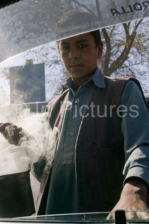 Street vendor waving spand, (smoking seeds burnt in a can) for good luck,