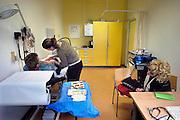 Nederland, Nijmegen, 11-7-2005Een vrouwlijke arts, huisarts, van de huisartsenpost, huisartsendienst, behandelt een patient in de spreekkamer. Avonddienst, bereikbaarheid, spoedgeval, ongelukje. Gezondheidszorg, eerstelijns zorg. Zorgverzekeraar, zorgverzekering. Basispakket. Basisverzekering.Foto: Flip Franssen