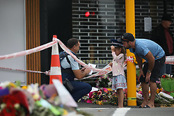 March 17, 2019 - Christchurch, New Zealand - A little girl wears police officer's cap as she shares a light moment with him outside the Linwood Masjid mosque in Christchurch on March 16, 2019. At least 49 people dead and more than 40 people injured following attacks on two mosques in  Christchurch. The national security threat level has been increased from low to high for the first time in New Zealand's history after this attack. (Credit Image: © Sanka Vidanagama/NurPhoto via ZUMA Press)